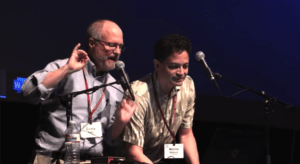 Curtis Loer and Morris Maduro speaking into microphones while hosting the Worm Show.