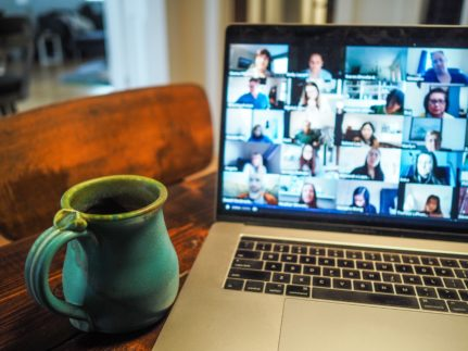 Laptop screen showing a video conference and cup of coffee.